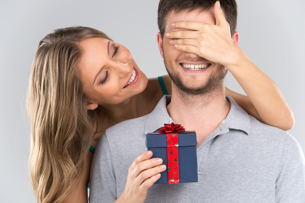 girl standing behind man with gift - gifts for a Cancer man